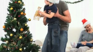 Father helping his son to decorate the Christmas tree against a white background