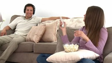Girl watching tv with popcorn while her boyfriend listens to music — Stock Video