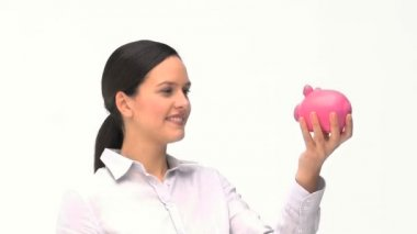 Woman putting dollars in a piggy bank — Stock Video #15459095