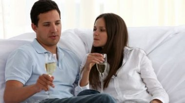 Couple toasting with champagne in the living room in a new home