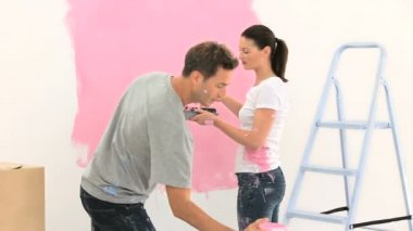 Pareja feliz pintando una pared en color rosa — Vídeo de stock