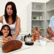Cute family having breakfast together - Stock Photo