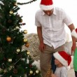 Father helping his son to put the star on top of the Christmas Tree — Stock Video