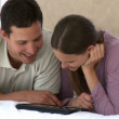 Stock Video: Happy couple using computer tablet sitting on couch