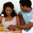 Couple having breakfast on the bed - Stock Photo