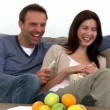 Stock Video: Lovely couple watching tv while sitting on sofa