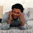 Man is angry on his cell phone on the bed - Stock Photo