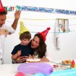 Cute boy blowing out candles for his birthday - Stockfoto