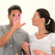 A man explains to his girlfriend how to paint - Stock Photo