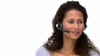 Closeup of a smiling businesswoman talking with headphones — Stock Video