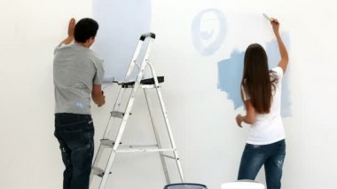 Happy couple painting wall in blue — Stock Video