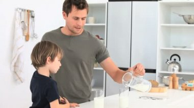Attentive man serving a glass of milk to his son — Stock Video