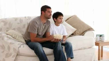 Father eating popcorn with his son — Stock Video