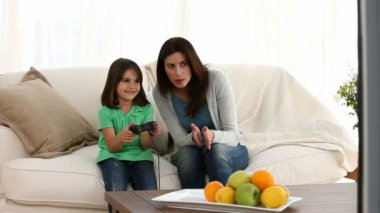 Cheerful mom encouraging her daughter to play video games — Vídeo Stock