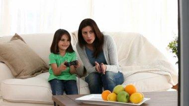 Mamá alegre alentando a su hija para jugar video juegos — Vídeo de Stock