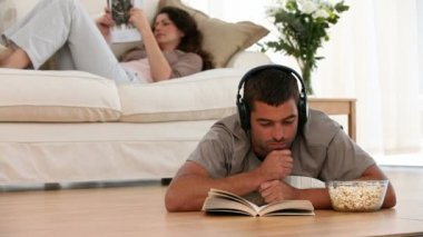 Man listening to music reading and lying on the floor while his wife looking at a magazine — Stok video