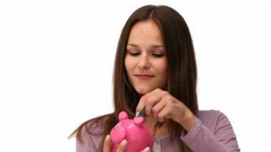 Woman putting money into a piggybank — Stock Video #15461643