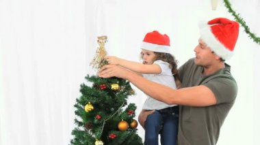 Man helping his daughter to decorate the Christmas tree at home