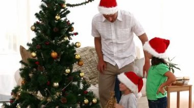 Father helping his son to put the star on top of the Christmas Tree — Wideo stockowe