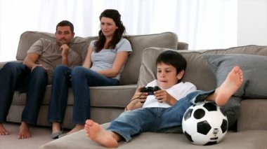 Cute little boy playing video games and parents enjoying watching — Stock Video