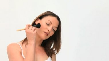 Beautiful women putting make up on against a white background
