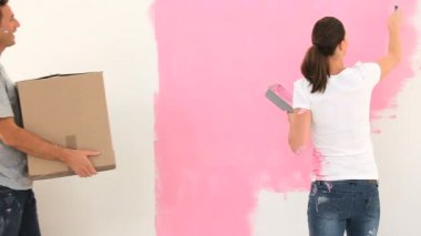 Young woman painting a wall and talking with her husband — Stock Video