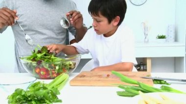 Father cooking a salad with her son — Stock Video