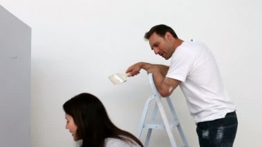 Couple painting a wall in white — Video Stock