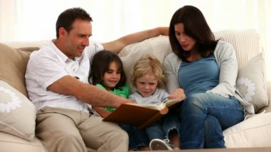 Cute family reading a book — Stockvideo