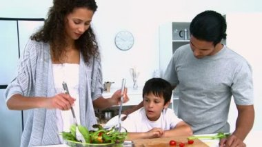 Woman cooking a salad with her son in the kitchen