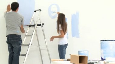 Young couple having fun while painting walls — Stock Video