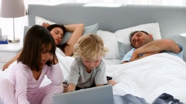 Attentive children using a laptop while their parents are sleeping — Stock Video