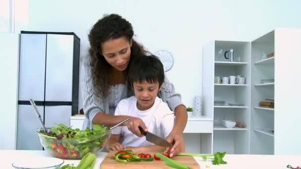 Madre cocinando una ensalada con su hijo — Vídeo de stock