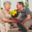 Retired couple holding a bunch of flowers — Stock Video #15530319
