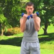 Stock Video: Musing blue dumbbells outdoors