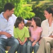 Family sitting on a park bench — Stock Video