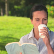 Woman having a drink and reading outdoors - 