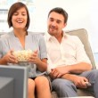 Stock Video: Young couple watching tv with popcorn