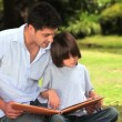 Father and son sitting reading outdoors — Video