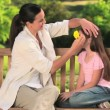 Mother putting a flower in her daughter's hair — Stock Video