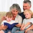 Grandsparents reading a book to their grandchildren — Stock Video #15535187