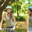 Athletic couple cycling in a wood — Stockvideo