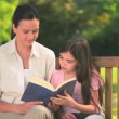 Mother and daughter reading outdoors — Stock Video