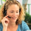 Curly-haired woman speaking over the headset — Stok video