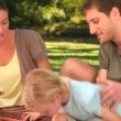 Happy family opening a picnic basket  in a par - Stock Photo