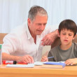 A man hepling his grandson to do his homeworks - Stock Photo