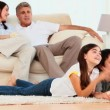 Family laughing in front of tv - Stock Photo