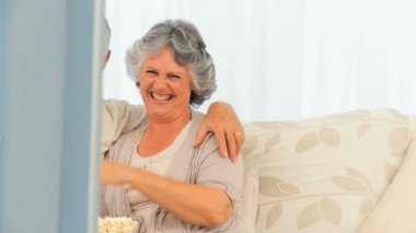 Senior couple eating popcorn in front of the tv — Stock Video