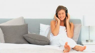 Lovely woman listening to music in her bed — Stock Video