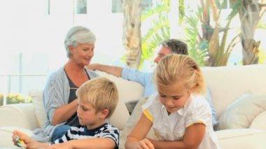 Grandparents talking while grandchild are makgin puzzle — Stock Video